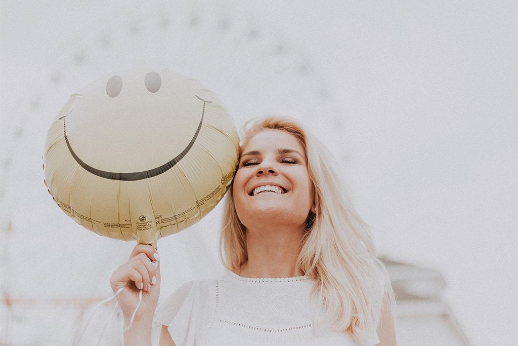 Woman Holding Smiley Balloon | Skinn Bar