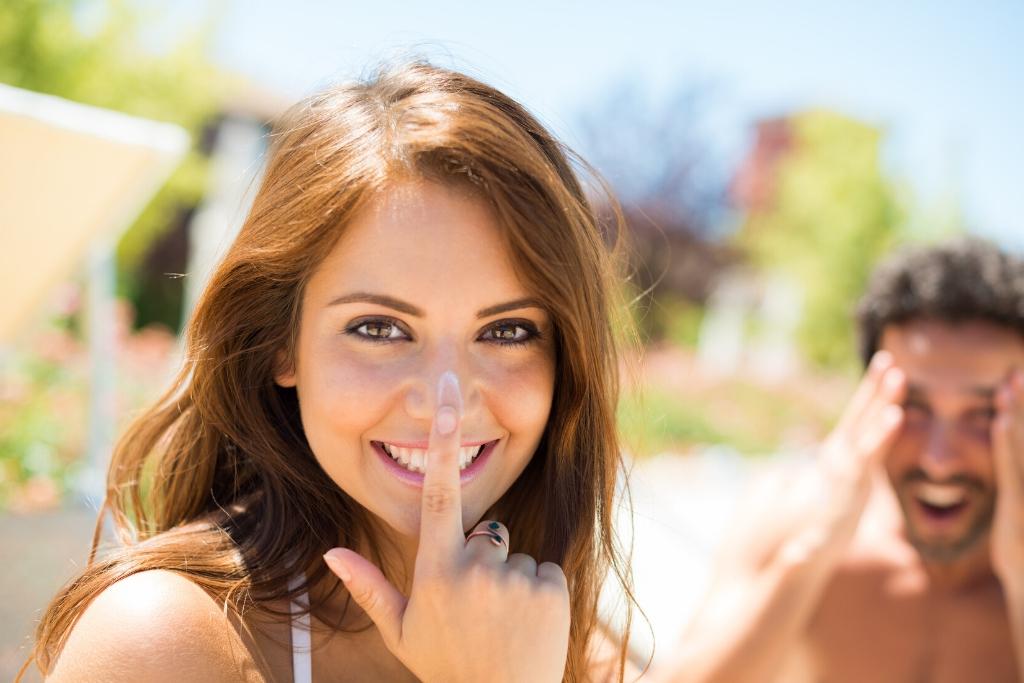 Happy Woman Applying Sunscreen In The Sun | Skinn Bar